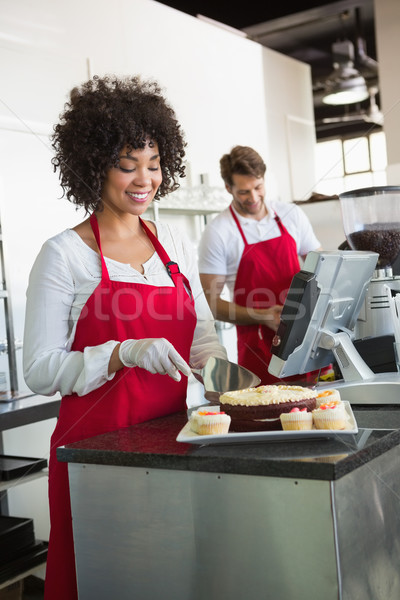 Pretty waitress slicing cake with waiter behind her Stock photo © wavebreak_media