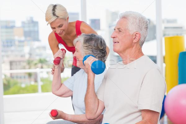 Senior man lifting dumbbells while trainer assisting woman at gy Stock photo © wavebreak_media
