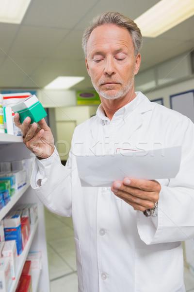 Pharmacist reading prescription and holding medicine Stock photo © wavebreak_media