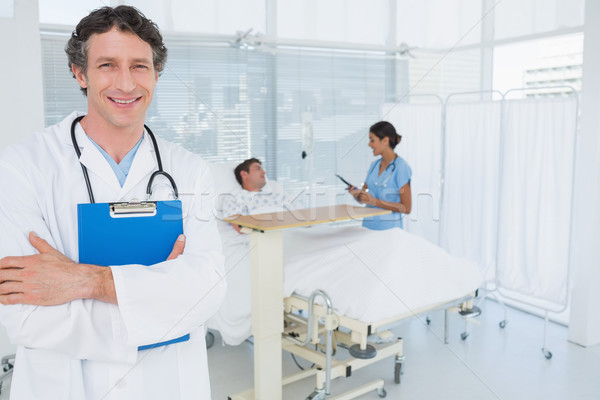Smiling doctor holding patients file Stock photo © wavebreak_media