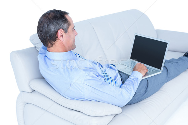 Smiling businessman lying on a sofa holding a laptop Stock photo © wavebreak_media