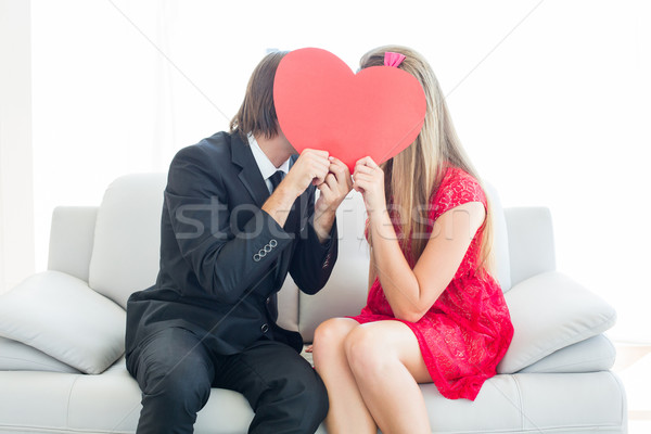 Cute geeky couple kissing and holding heart over faces Stock photo © wavebreak_media