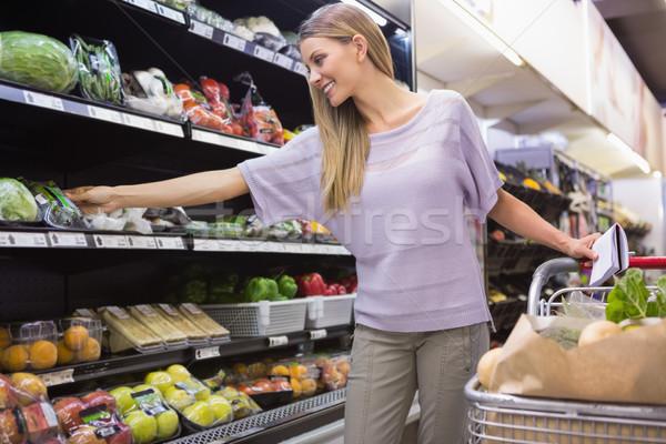 Glimlachende vrouw lezing notepad gangpad supermarkt vrouw Stockfoto © wavebreak_media