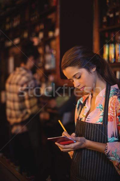 Pincérnő elvesz rendelés jegyzettömb pult kocsma Stock fotó © wavebreak_media