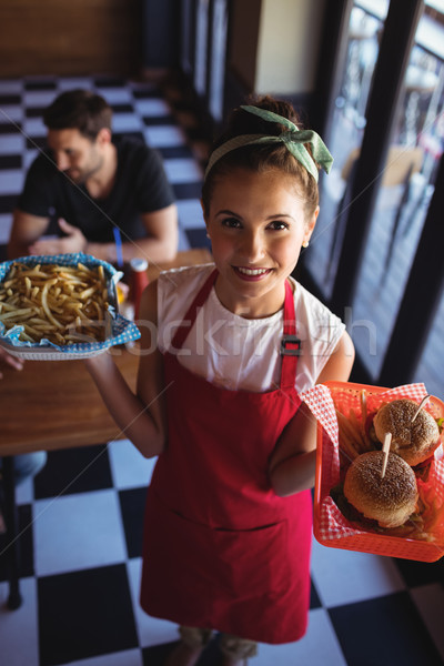 Waitress holding burger and french fries in tray Stock photo © wavebreak_media