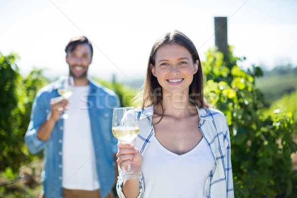 Stock photo: Smiling young couple posing with wineglasses at vineyard