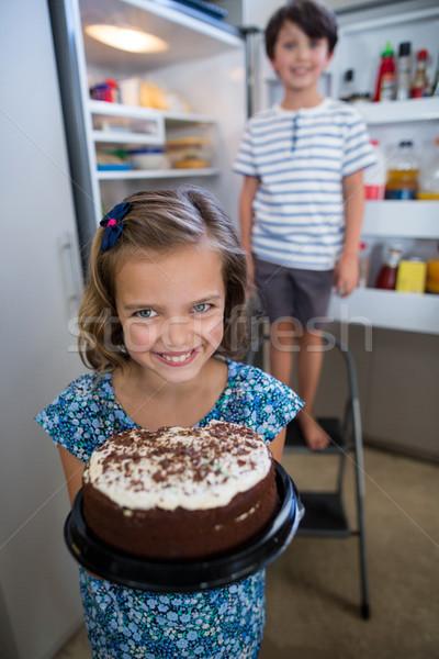 Portrait of girl holding cake in kitchen Stock photo © wavebreak_media
