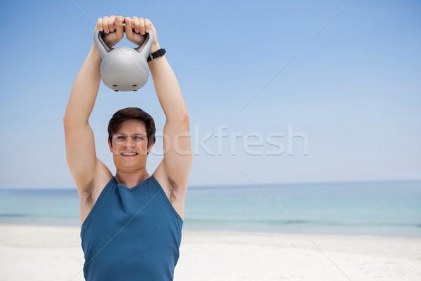 Stock photo: Young man lifting kettlebell at beach