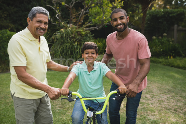 Father and grandfather helping boy while riding bicycle Stock photo © wavebreak_media