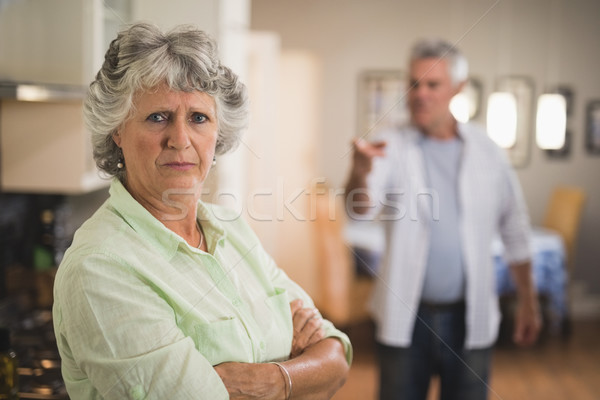 Portrait of unsmiling senior woman with angry man in background Stock photo © wavebreak_media