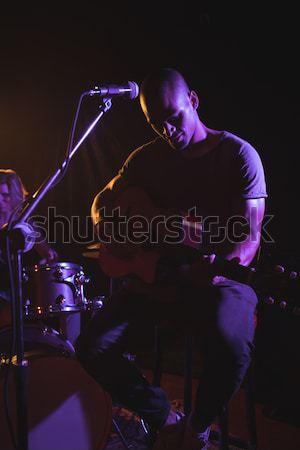 Confident female drummer and guitarist performing on illuminated stage Stock photo © wavebreak_media