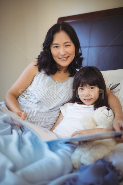 Mother and daughter holding book on bed in bed room Stock photo © wavebreak_media