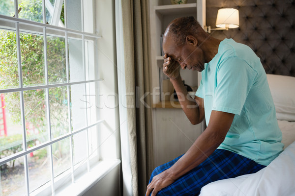 Side view of sad senior man sitting on bed by window at home Stock photo © wavebreak_media