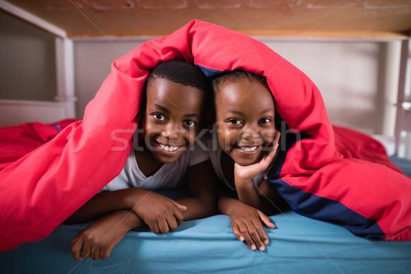 Retrato sorridente irmãos cobertor cama casa Foto stock © wavebreak_media