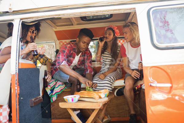 Happy friends holding beer bottles while sitting in camper van Stock photo © wavebreak_media