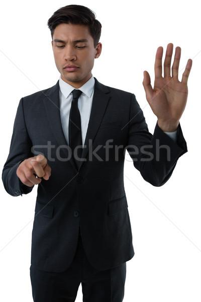 Fiatal üzletember láthatatlan interfész áll fehér Stock fotó © wavebreak_media