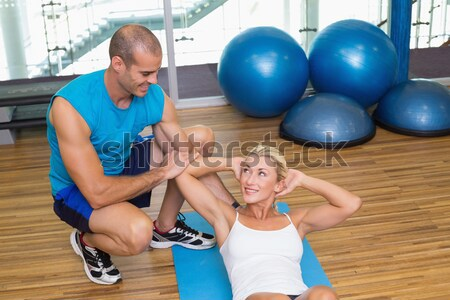 Physiotherapist assisting senior woman in performing exercise on fitness ball Stock photo © wavebreak_media