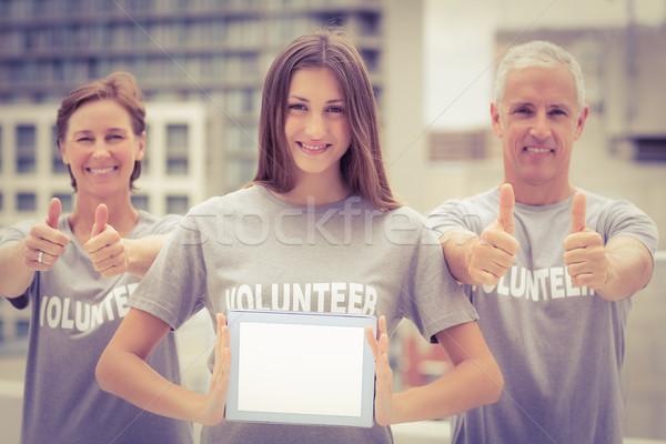 Mosolyog önkéntesek mutat tabletta portré tető Stock fotó © wavebreak_media