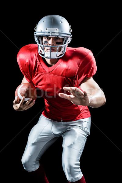 Portrait of defensive sportsman holding American football Stock photo © wavebreak_media
