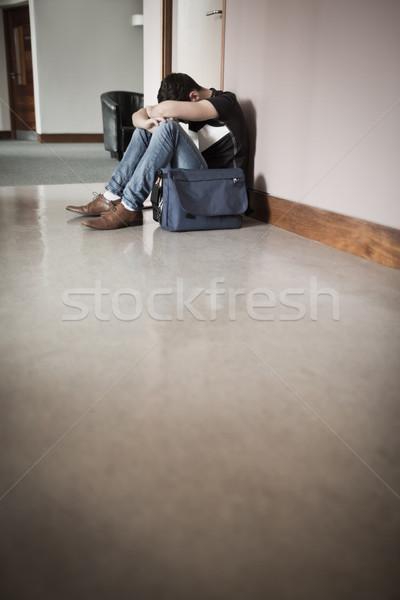 Maschio studente testa seduta muro college Foto d'archivio © wavebreak_media