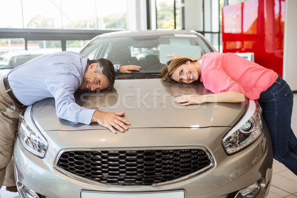 Casual smiling couple hugging their new car Stock photo © wavebreak_media