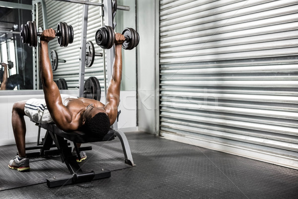 Shirtless man lifting dumbbells on bench Stock photo © wavebreak_media
