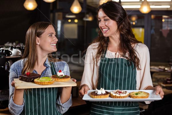 Pretty baristas holding desserts Stock photo © wavebreak_media