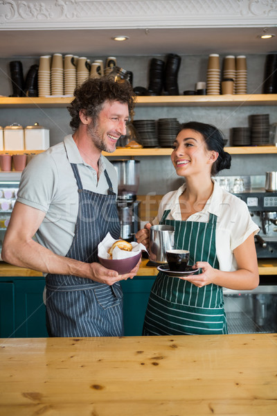 Waiter and waitress holding bowl with snack and coffee cup Stock photo © wavebreak_media