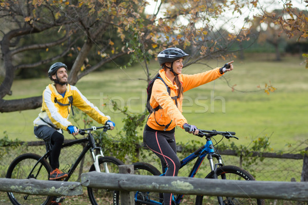 Biker couple cycling and pointing in distance Stock photo © wavebreak_media