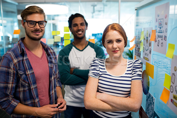 Stock photo: Smiling creative business team standing next to sticky notes in office