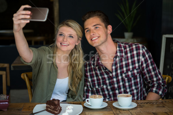 Smiling couple taking selfie with cell phone in cafeteria Stock photo © wavebreak_media