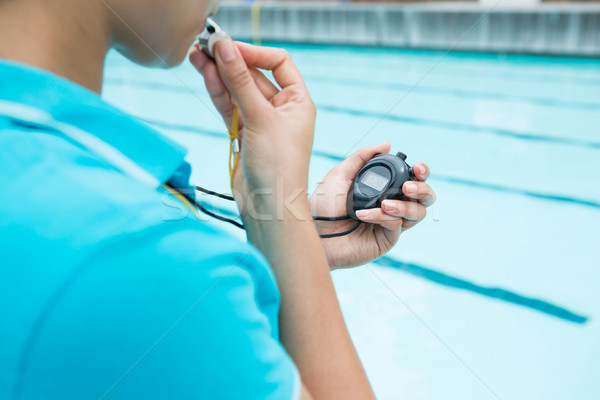 Female coach blowing whistle and looking at stopwatch Stock photo © wavebreak_media