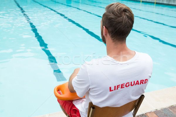 Lifeguard sitting on chair with rescue buoy at poolside Stock photo © wavebreak_media