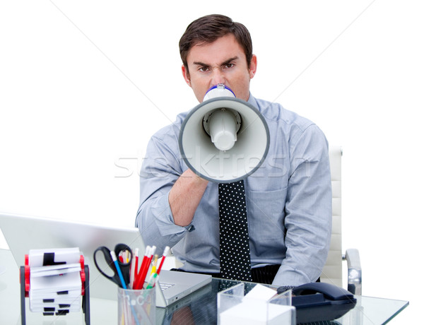 Furious businessman yelling through a megaphone sitting at his d Stock photo © wavebreak_media