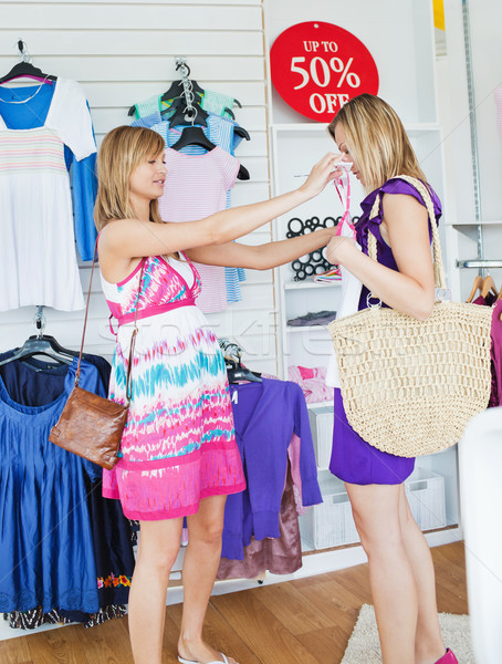 Cheerful women choosing clothes together in a shop  Stock photo © wavebreak_media