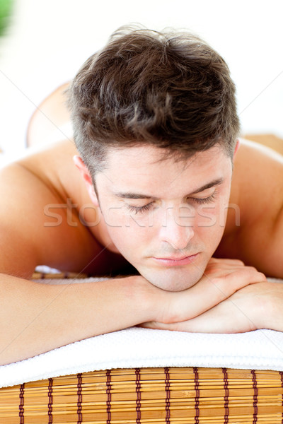 Caucasian relaxed young man lying on a massage table in a spa center Stock photo © wavebreak_media