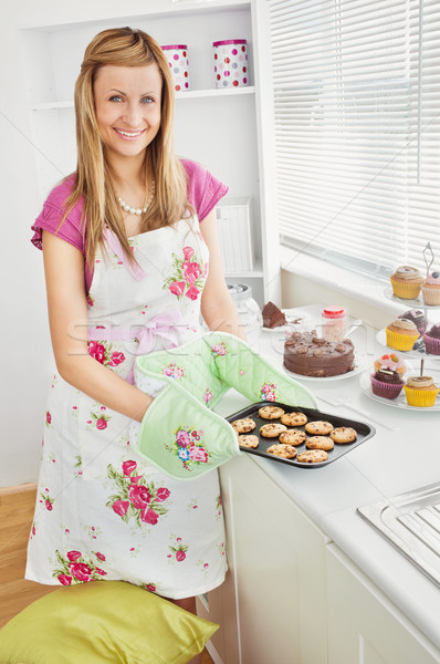 Positive young woman baking cookies in the kitchen at home Stock photo © wavebreak_media