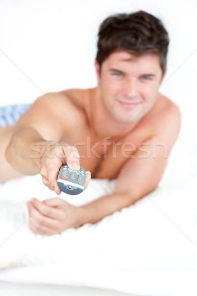 bare-chested man with pyjamas using a remote lying on his bed at home Stock photo © wavebreak_media
