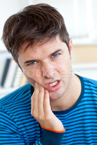 Cute caucasian man having a toothache in the living-room at home Stock photo © wavebreak_media