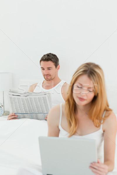 женщину ноутбука муж чтение газета кровать Сток-фото © wavebreak_media