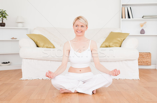 Attractive blonde woman practicing yoga at home Stock photo © wavebreak_media