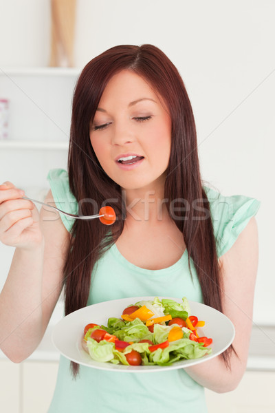 Pretty red-haired woman enjoying a mixed salad in the kitchen in her appartment Stock photo © wavebreak_media