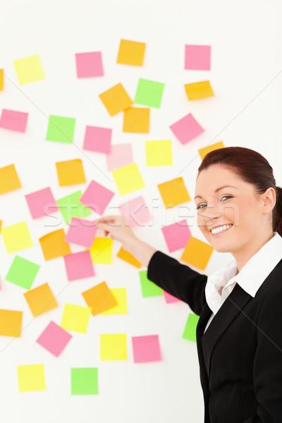 Mosolygó nő jegyzetek fehér fal iroda munka Stock fotó © wavebreak_media