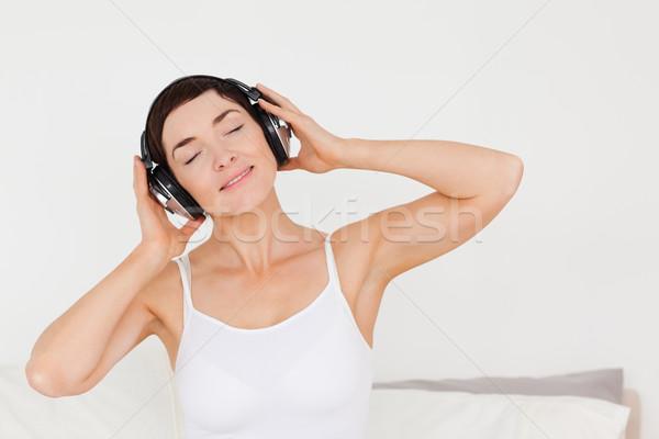 Delighted woman listening to music in her bedroom Stock photo © wavebreak_media