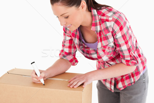 Portrait of a beautiful woman writing on cardboard boxes with a marker while standing against a whit Stock photo © wavebreak_media