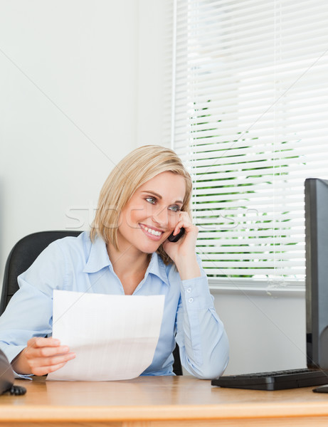 Businesswoman smiling at screen while phoning and holding a paper in her office Stock photo © wavebreak_media