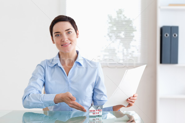 Short-haired Woman holding papers pointing at a model house in an office Stock photo © wavebreak_media