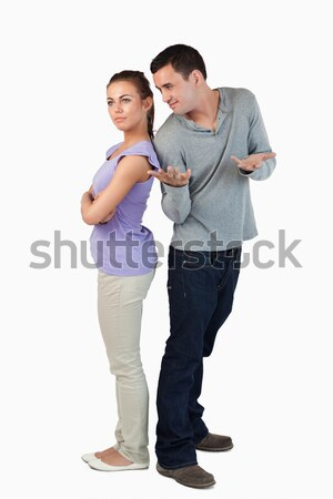 Young couple standing back-to-back to each other against a white backgrounf Stock photo © wavebreak_media