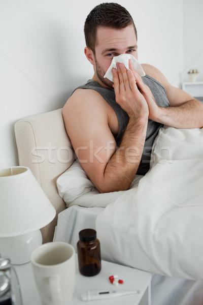 Portret jonge man blazen neus slaapkamer hand gezicht Stockfoto © wavebreak_media