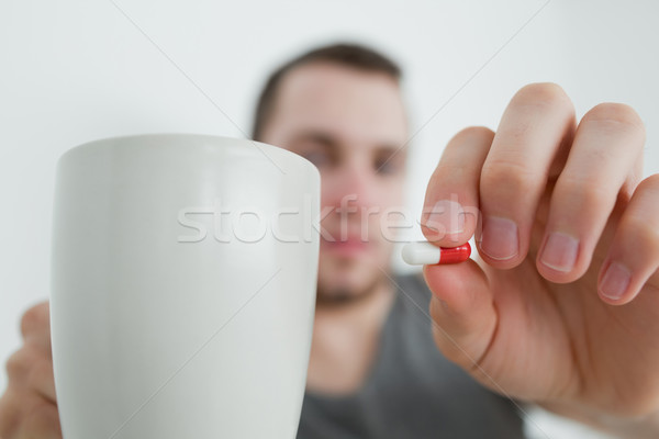 Man showing a pill and and a mug in his bedroom Stock photo © wavebreak_media